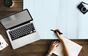 Un escritorio con computadora y cuaderno.