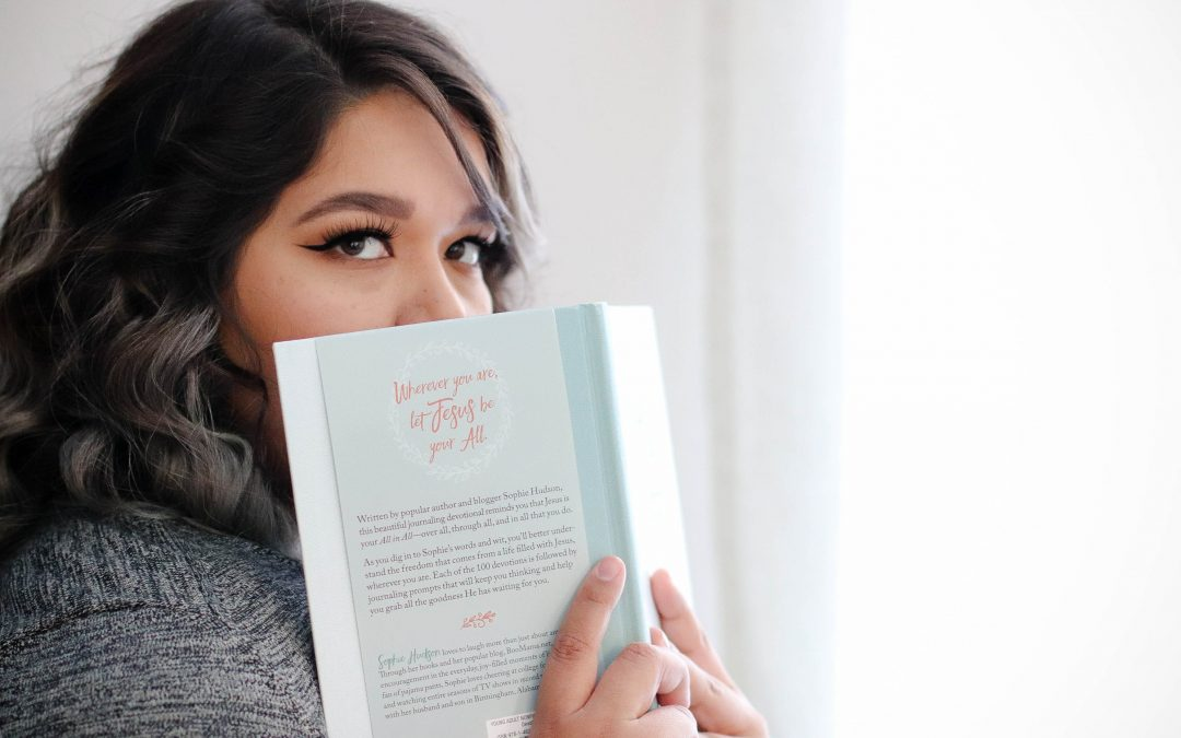 A girl peeks with interest over a book.